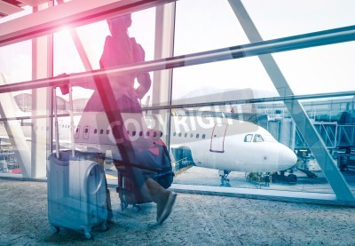 Poster Travel concept with woman and suitcase moving fast to airport terminal gate - Double exposure look with focus on the aircraft in the background - Violet marsala sun flare with vintage filtered editing