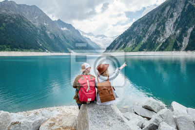 Poster Travelers couple look at the mountain lake. Travel and active life concept with team. Adventure and travel in the mountains region in the Austria. Travel - image
