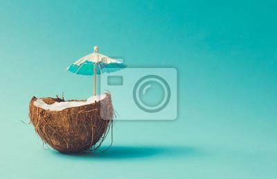 Poster Tropical beach concept made of coconut fruit and sun umbrella. Creative minimal summer idea.