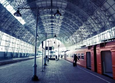 Poster Überdachter alter Bahnhof mit Zug und Silhouetten von Menschen