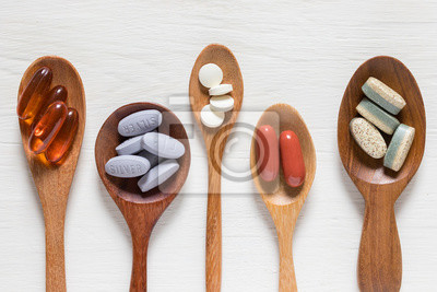 Poster Variety of vitamin pills in wooden spoon on white background, supplemental and healthcare product, flat lay surface