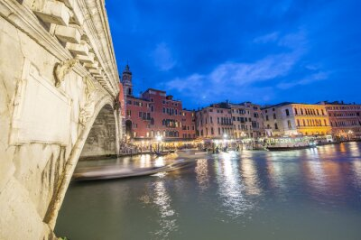 VENICE, ITALY - APRIL 2014: Rialto Bridge at night with city restaurants along grand canal