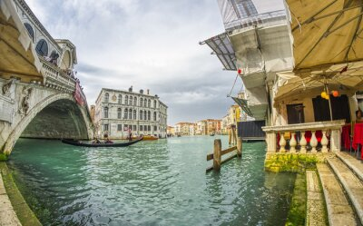 VENICE, ITALY - APRIL 2014: Tourists enjoy the view of Rialto Bridge on a cloudy day