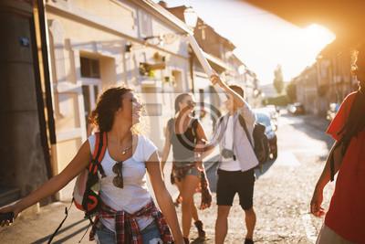 Poster Vier attraktive Studenten, die einen sonnigen Tag von Ferien in einer anderen Stadt genießen.
