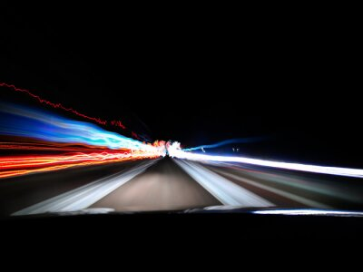 Poster View of night highway neon lights on long exposure from car's front window near a city