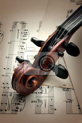 Violin peg box and scroll on music sheet. Vintage style.