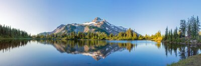 Poster Volcanic mountain in morning light reflected in calm waters of lake.