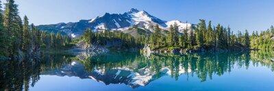 Poster Vulkanischer Berg im Morgenlicht spiegelt sich in ruhigem Wasser des Sees.