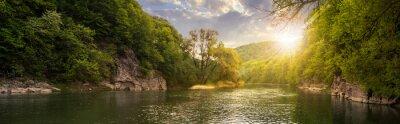 Poster Wald Fluss mit Steinen am Ufer bei Sonnenuntergang