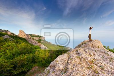 Wanderer an der Spitze eines Felsens mit seinen Händen genießen sonnigen Tag