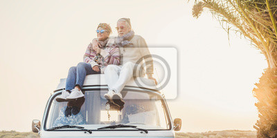 Poster Wanderlust and travel destination happiness concept with old senior beautiful couple sitting and enjoying the outdoor freedom on the roof of vintage van vehicle together - sun backlight