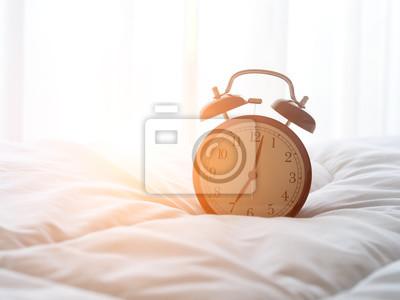 Poster Wecker auf dem Bett am Morgen mit Sonnenlicht ..