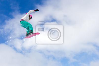 Weiblicher Snowboarder macht einen tollen großen Sprung aus einem Kicker
