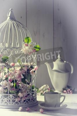 Poster Weinlese-Nachmittagstee mit Birdcage mit Frühlingsblüte gefüllt