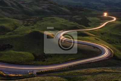 Poster Winding curvy ländlichen Straße mit Lichtweg von Scheinwerfern durch britische Landschaft.