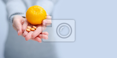 Poster Woman holding tangerine and vitamin C, medecine, health care on gray light background, space for text