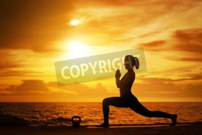 Poster woman practicing yoga during surrealistic sunset at the seaside. healthy concept and workout.