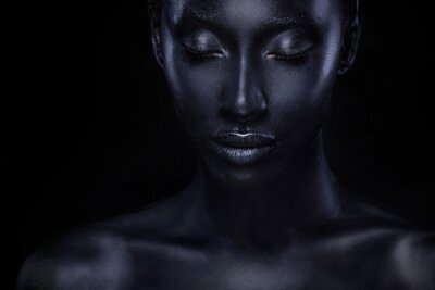 Poster Woman with black body paint. Cheerful young african girl with bodypaint. An amazing model with art makeup. Closeup face.
