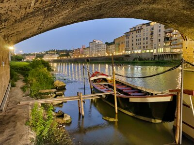 Wooden boat underneath Old Bridge and Florence Lungarni at night. Panoramic cityscape in Autumn, Tuscany - Italy