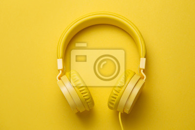 Poster Yellow headphones on yellow background. Music concept.