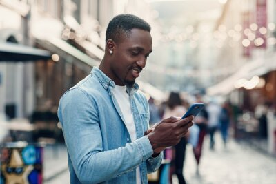 Poster Young african american man standing on the summer street and using smart phone.