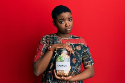 Poster Young african american woman holding savings jar with south african rands money skeptic and nervous, frowning upset because of problem. negative person.