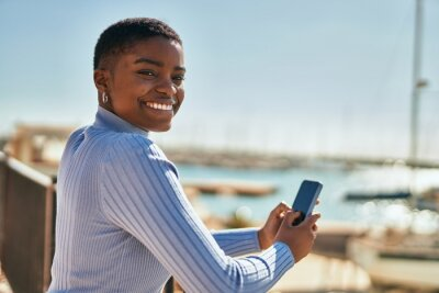 Poster Young african american woman smiling happy using smartphone at the port
