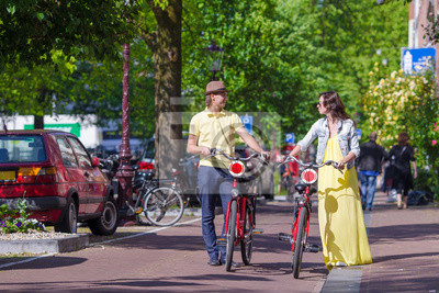 Young happy caucasian couple on bikes in old streets in