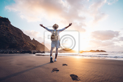 Poster Young man arms outstretched by the sea at sunrise enjoying freedom and life, people travel wellbeing concept
