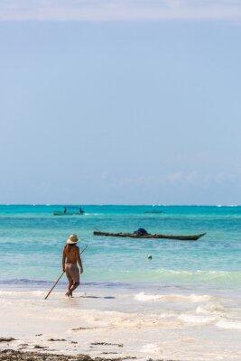 Young man dressing a safari hat walking in a tropical beach in Tanzania, Africa