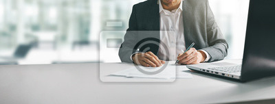 Poster young man in suit writing business papers at desk in modern coworking office. copy space