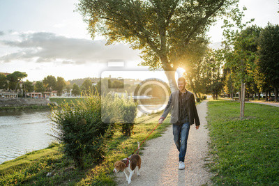 Poster Young man takes his beloved dog for a walk in the park at sunset - Millennial in a moment of relaxation with his four-legged friend