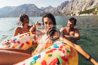 Poster Young trendy people having fun swimming in summer vacation