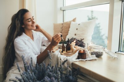 Poster Young woman applying natural organic essential oil on hair and skin. Home spa and beauty rituals.