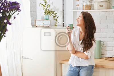 Poster Young woman drinking a morning coffee in kitchen