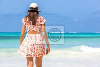 Young woman enjoying a beautiful blue beach in Zanzibar, Tanzania