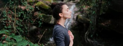 Poster Young woman practicing breathing yoga pranayama outdoors in moss forest on background of waterfall. Unity with nature concept.