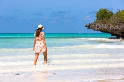 Young woman wearing a hat in a amazing blue water beach in Zanzibar in Tanzania