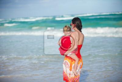 Zurück von Mutter und Tochter in roten Kleid zu Fuß am Strand