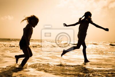 zwei Kinder Silhouetten laufen am Strand bei Sonnenuntergang