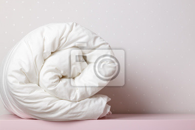 Sticker A folded, warm duvet is lying on the dressing table. Quilt for the bed. Copy space