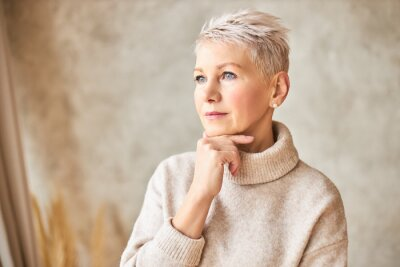 Sticker Aging, beauty, style, elegance and fashion concept. Portrait of thoughtful middle aged lady wearing beige turtleneck sweater with hand under chin, pondering, having worried facial expression