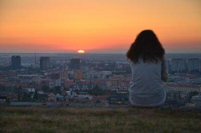 Allein junges Mädchen sitzen über Stadt und Blick auf ruhige Sommer Sonnenuntergang.