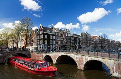 Sticker Amsterdam-Kanal-Kreuzung mit roten Kreuzfahrtschiff im Sommer mit einem blauen Himmel