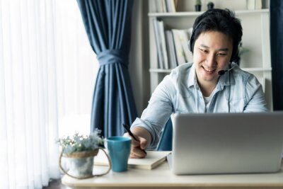 Sticker Asian businessman talking to colleague team in video call conference writing note on book with smile face. Man using computer laptop and headphone for online meeting. Smart working from home concept.