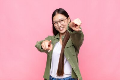 Sticker asian young woman feeling happy and confident, pointing to camera with both hands and laughing, choosing you