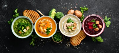 Sticker Assortment of colored vegetable cream soups. Dietary food. On a black stone background. Top view. Free copy space.