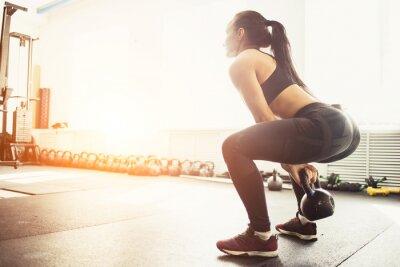 Sticker Athletische Frau, die mit Kesselglocke trainiert, während sie in der Hockeposition ist. Muskulöse Frau, die Crossfit-Training im Fitnessstudio macht.