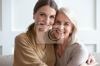 Sticker Attractive aged mother and adult daughter hugging looking at camera