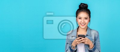 Sticker Banner of Portrait happy asian woman feeling happiness and looking camera holding smartphone on blue background. Cute asia girl smiling wearing casual jeans shirt and connect internet shopping online